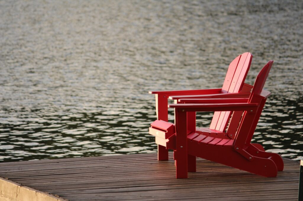 red-wooden-lounge-chair-on-brown-boardwalk-near-body-of-161029